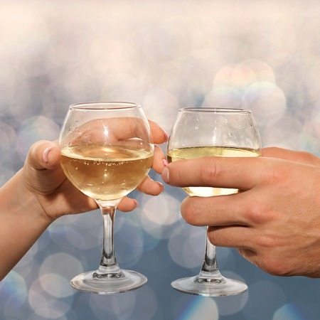 Loving couple clink glasses with white wine. Closeup hands man and woman hold glasses of champagne Stock Photo