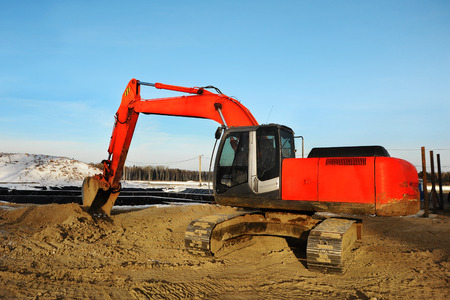 Heavy big red excavator working on new construction site Stock Photo
