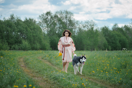 Portrait of a beautiful girl in Slavic clothes. Young woman with a Siberian husky dog. Summertime Stock fotó - 81452165