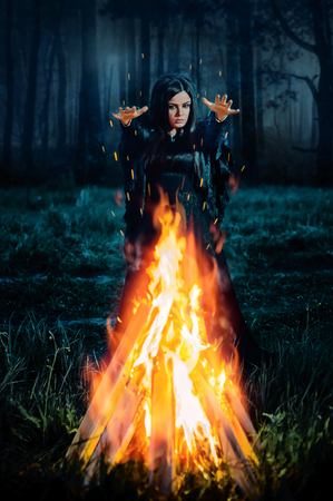 A young witch in a black dress conjures at the fire at night in the forest. Priestess of fire. Fantasy illustration. Fairytales Stock Photo