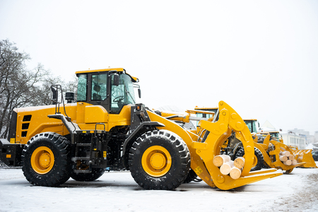 Yellow wheel front end log loader. Forestry equipment for moving wood and other materials. Hydraulic manipulator. Heavy diesel tractor, industrial machinery. Winter time Stock fotó - 115470514