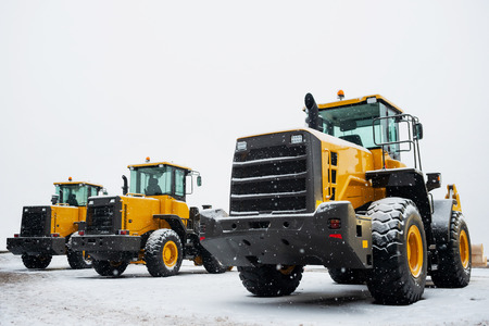 Yellow wheel front loaders. Construction and handling equipment. Heavy diesel tractor, construction machinery, industrial vehicle. Winter time Reklamní fotografie
