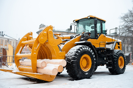 Yellow wheel front end log loader. Forestry equipment for moving wood and other materials. Hydraulic manipulator. Heavy diesel tractor, industrial machinery. Winter time Stock Photo