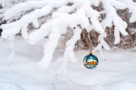 Christmas blue ball hanging on a snowy branch. Festive decoration in the winter forest. Merry Christmas and Happy New Year Stock Photo