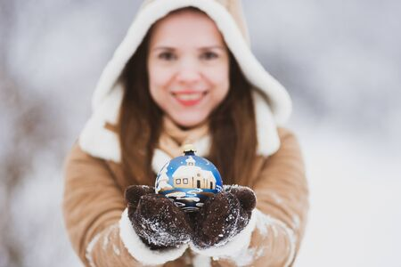 Smiling girl holding a Christmas ball in her hands outdoors. Merry Christmas and Happy New Year. Stock Photo