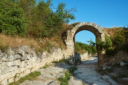 Stone arch on the street of an ancient abandoned city. The ruins of the old city. Sunny summer day, clear blue sky.