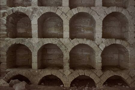 Ancient empty wine warehouse inside a cave. Old stone arches used to store bottles of wine.