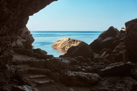 Inside view of the grotto to the sea. Dark cave in the mountains. Big stones. Black Sea
