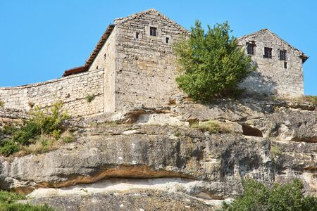 Ancient abandoned building on a cliff top. Stone house over a cliff. Sunny summer day, clear blue sky.