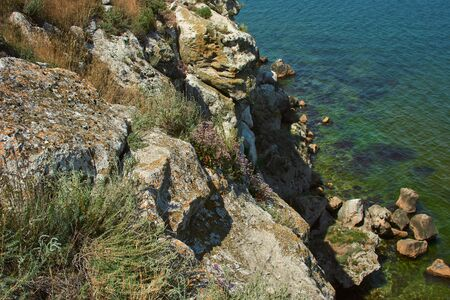 Dangerous rocky cliffs jagged to ocean. Peaked rocks and cliffs on the seashore