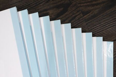 Stack of books with a blue hard cover on wooden background. Composition from books