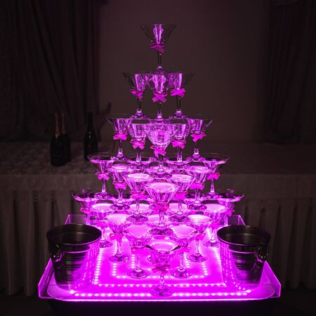 Pyramid of glasses for beverages, wine, champagne. Festive decoration for event, wedding, party. Wine glasses in neon light
