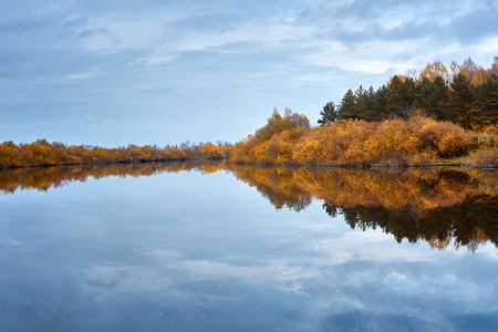 Autumn forest by the river. Autumn trees reflected in calm water. Colorful fall landscape. Indian summer.