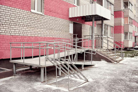 Ramp for baby strollers and wheelchairs with metal handrails at the entrance to the residential building 版權商用圖片