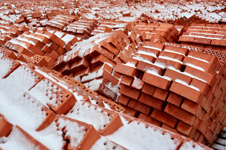 Stack of red clay bricks on construction site. Wintertime 版權商用圖片