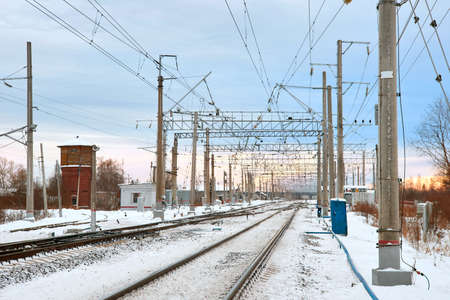 Railroad tracks at sunset in winter time. Railway infrastructure. Steel railway for trains in snow.