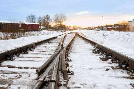 Railroad tracks at sunset in winter time. Close-up of railway tracks with crossing. Railway infrastructure. Steel railway for trains in snow.