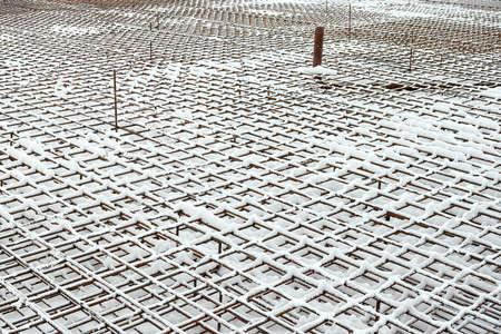 Metal armature net for building construction. Reinforcements steel bars stack. Building materials, formwork, metal structures. Construction site in winter.