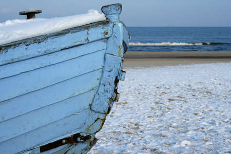 Old blue wooden boat at the seaside during winter time. Stock Photo