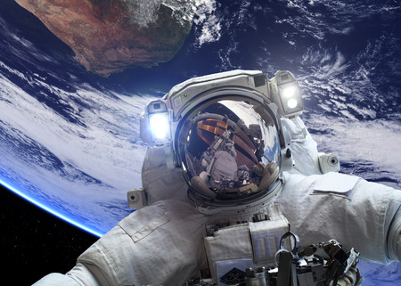 cosmonaut: Astronaut in outer space against the backdrop of the planet earth.