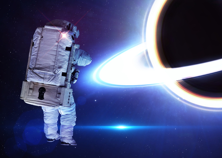 black hole: Astronaut in outer space against the black hole.