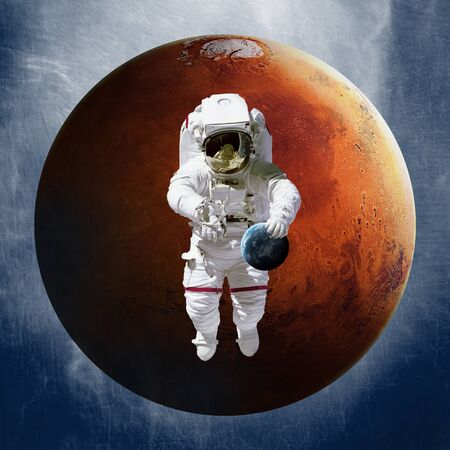 Astronaut, holding a planet Earth in hand on against of Mars. Stock fotó