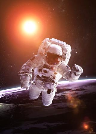 惑星の背景に宇宙空間で宇宙飛行士。 写真素材