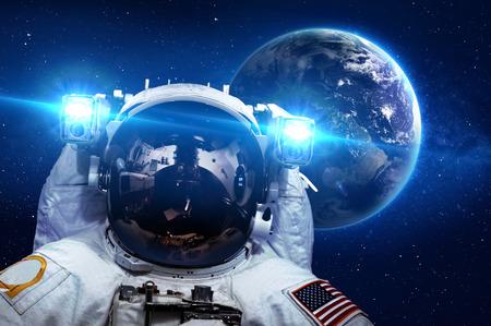 sol y luna: Astronauta en el espacio exterior contra el telón de fondo del planeta. Foto de archivo