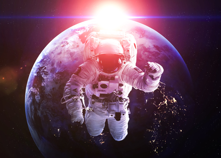 gravity: An astronaut floats above Earth. Stars provide the background.  Stock Photo