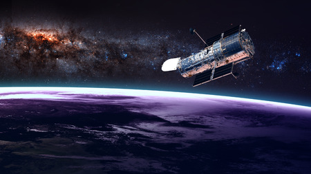 The Hubble Space Telescope in orbit above the Earth. Elements of this image furnished by NASA. Stock Photo