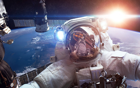 orbital spacecraft: International Space Station with astronaut over the planet Earth
