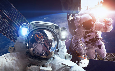 orbital spacecraft: International Space Station with astronauts over the planet Earth Stock Photo