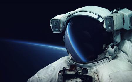 宇宙遊泳で宇宙飛行士。宇宙アート、サイエンス フィクションの壁紙。宇宙服のバイザーで反射します。宇宙の銀河の数十億。NASA から提供された