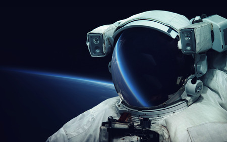 Astronaut at spacewalk. Cosmic art, science fiction wallpaper. Reflection in spacesuit vizor. Billions of galaxies in the universe. Elements of this image furnished by NASA