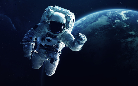 Astronaut in front of the Earth planet. Elements of this image furnished by NASA Stock Photo