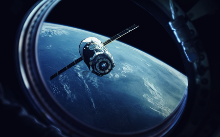 View from spaceship porthole. Earth and spacecraft. Elements of this image furnished by NASA Stock Photo