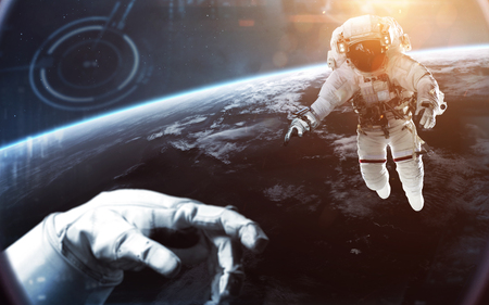 Brave astronauts looking at the beautiful blue  Earth. People in space. Elements of this image furnished by NASA