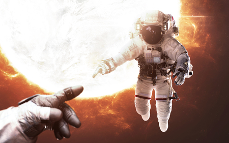 Two brave astronauts in front of burning star. Human in space. 版權商用圖片 - 100349850