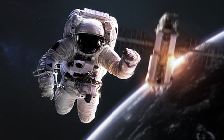 Astronaut at spacewalk, satellite orbiting Earth planet. Stock Photo