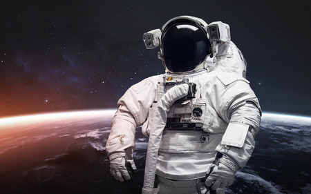 Astronaut at the spacewalk. Awesome beautiful Earth planet in cold and warm light.