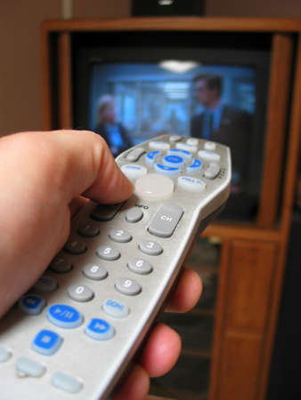 A close up shot of a person using a remote control pointed at a television