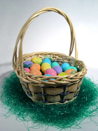 An Easter Basket Sitting On Easter Grass with Easter Eggs Inside Stock Photo