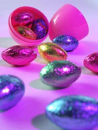 An open plastic Easter egg revealing colorful chocolate eggs inside