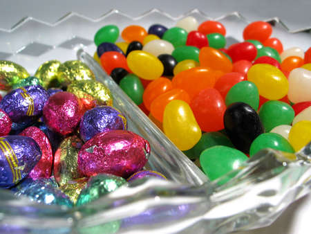 A close-up of a candy dish with Easter jellybeans and chocolate eggs inside