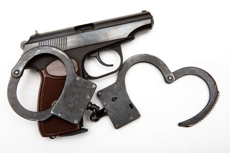 gun and handcuffs on a white background