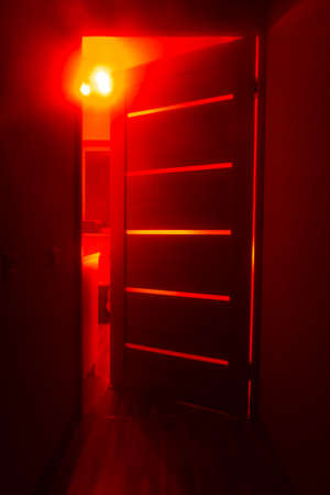 Bright red light from the room through the door. Abstract mystical glowing exit