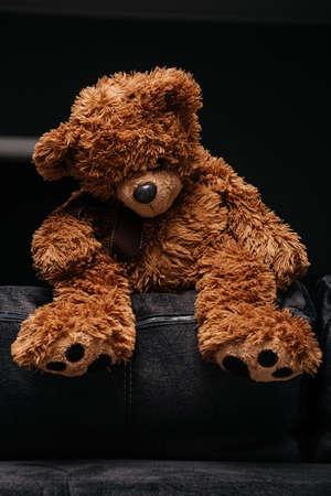sad teddy bear sitting on the back of the sofa Standard-Bild
