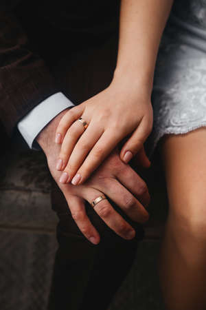 The hands of the newlyweds. The bride and groom got married and, holding hands, showed their wedding rings.