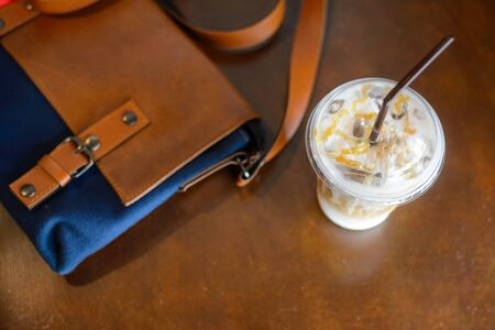 leather bag: Coffee in plastic cups and leather bag