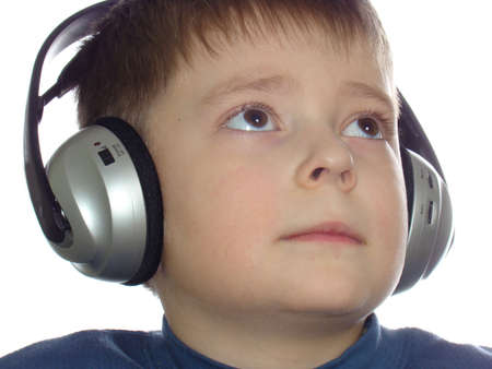 Boy listening music in headphones isolated over white background                                Stock Photo